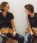 Two women laughing with guns and toolbelts