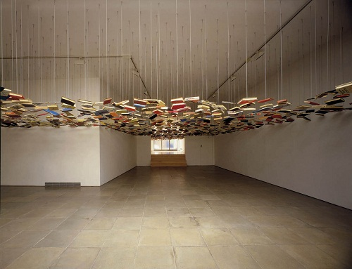 An empty room with a cloud of second-hand books suspended from the ceiling