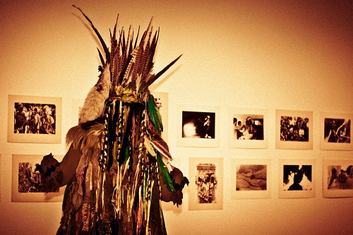 A figure standing in an art gallery wearing a spiky headdress and trailing ribbons