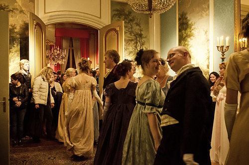 Dancers wearing costumes from the early nineteenth century in a historic house at night