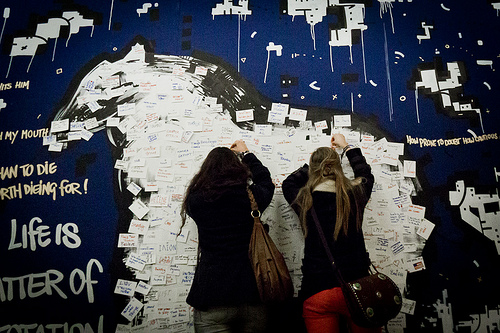Two girls sticking post-it notes with writing on to an art installation shaped like a horse