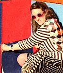 A woman in sunglasses by a multicoloured wall