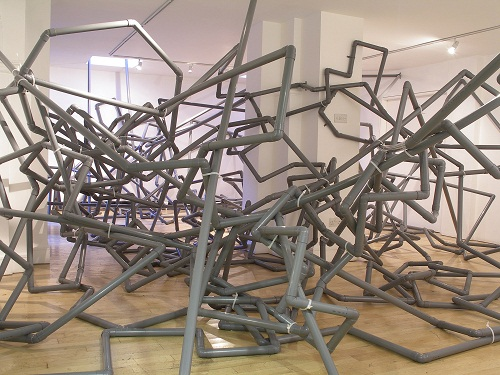 A room filled with a twisting sculpture made of grey plumbers' pipes