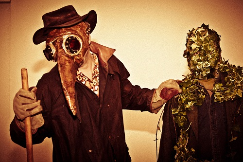 2 people, one wearing a beaked plague doctor mask, one with leaves covering his face