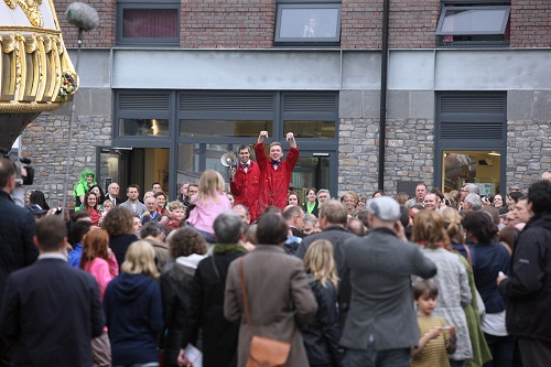 Two men in red boiler suits by the golden prow of a ship surrounded by a crowd of people