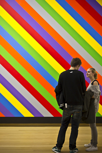 A man and a woman in front of multi-coloured diagonal stripes