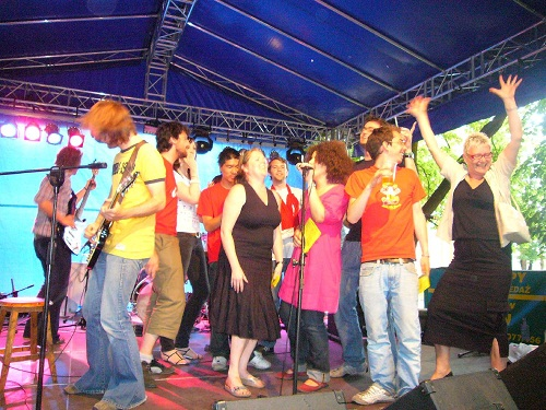 A colourful group of people singing and dancing on an outdoor stage
