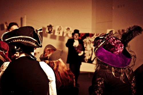 People with elaborate hats watching a performance