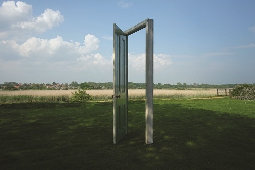 A doorframe and open door in the middle of the countryside