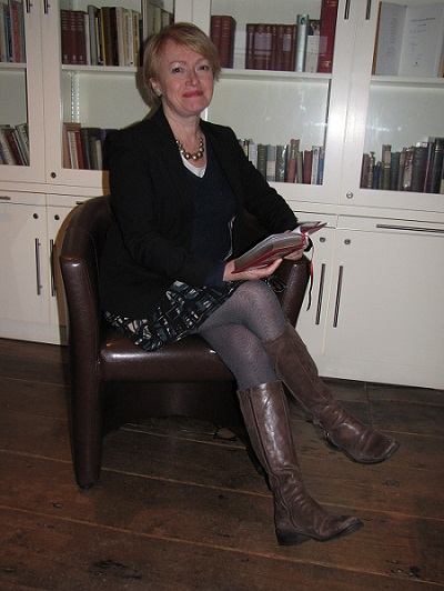 A woman sitting in front of a bookshelf holding a red hardback book