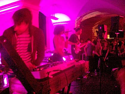 A band performing in a museum basement, lit with magenta light