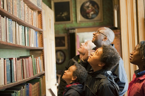 A group of people looking at a bookshelf in a historic library