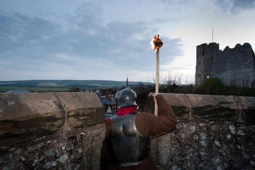 Soldier on castle ramparts holding blazing torch at dusk