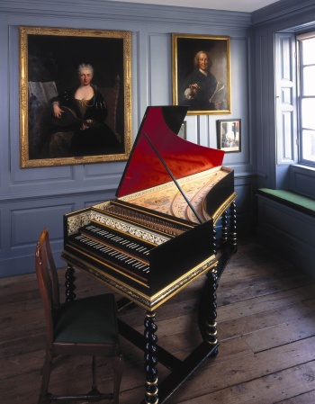An open harpsichord in the corner of a room with pictures on the wall.
