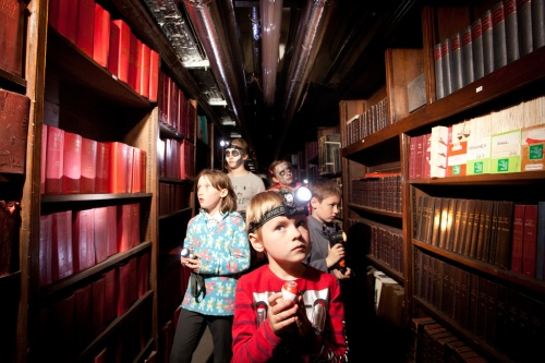 children walking between bookcases