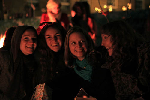 four smiling women in a garden at night