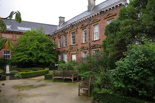 Exterior of a historic building with trees and benches