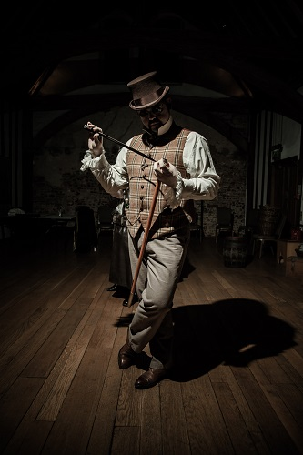A sinister Victorian man with a cane, riding crop and top hat
