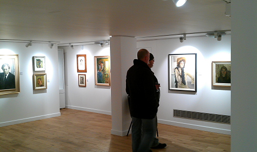 Two visitors view artwork a gallery