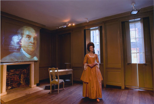 A woman in 18th century costume inside a historic building