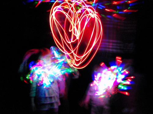 People creating colourful light trails in a dark room