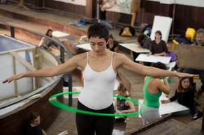 A hula-hoop dancer performing in a gallery