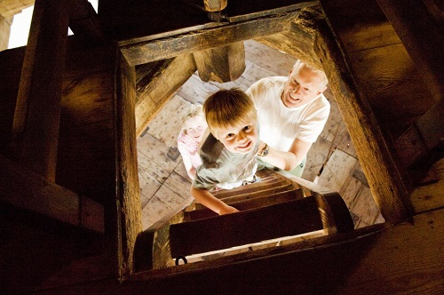 Grandparents look on as a small boy climbs a ladder up in to a historic loft