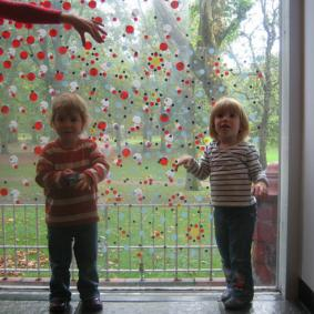Two toddlers covering a window with colourful spotty stickers
