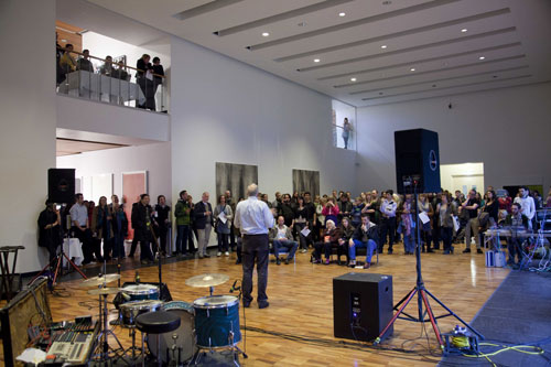 A man speaks to a large crowd in an art gallery