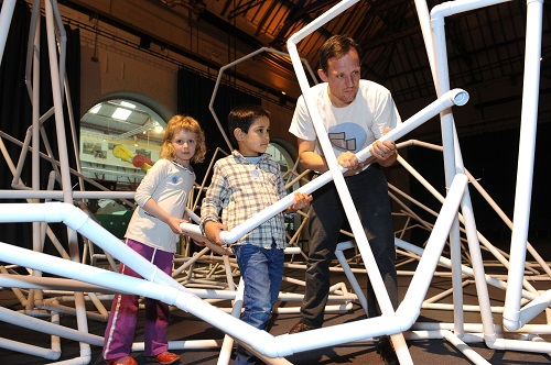 A man and two children constructing an enormous sculpture from white plastic pipes