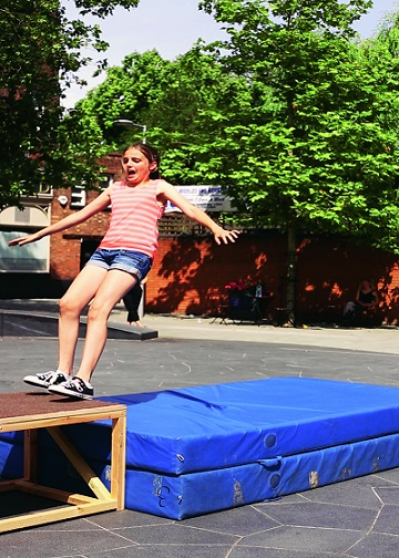 A girl falling backwards onto crashmats