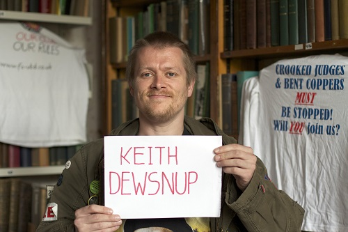 A man holding a sign with his name on in a library, with a t shirt hanging up behind him