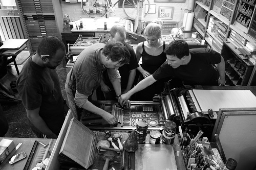 A group of people putting type together for a letterpress printer
