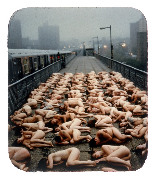 A group of nude bodies lying in an urban landscape