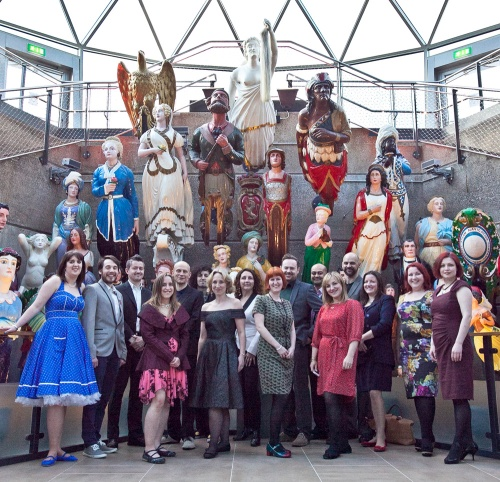 A group of glamorous people standing by a display of ships' figureheads