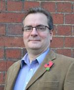 A man in a jacket wearing a poppy