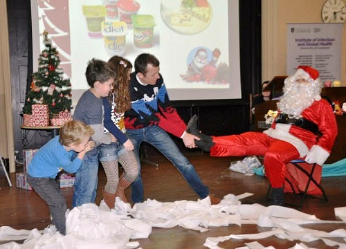 A group of children attempting to pull of one of Father Christmas' boots.
