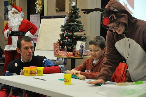 Children and a person in a reindeer suit playing with playdough