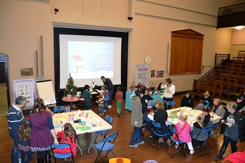 Children gathered around tables doing craft activities