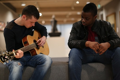 Two teenagers playing a guitar