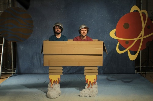 Two men in a cardboard box with colanders on their heads