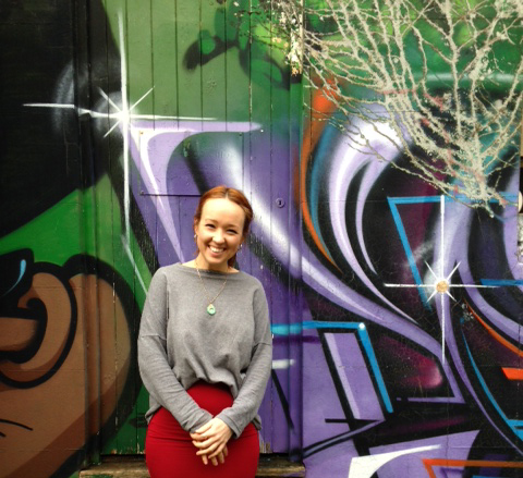 A smiling girl in a red skirt standing in front of a painted wall.