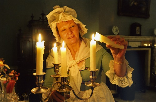 A woman in period costume lighting a candelabra