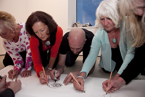 Adults drawing on a large piece of paper on the ground