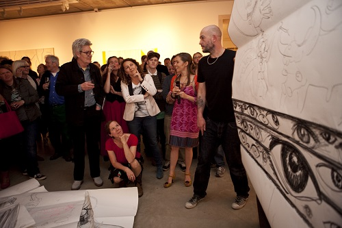 A group of people in an art gallery looking at a large drawing