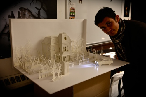A man setting up an intricate paper sculpture