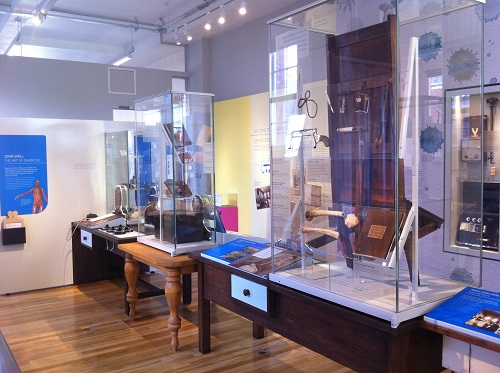 Tables with cabinets displaying an assortment of artifacts. Information on the walls to read and a set of headphones resting on a table.