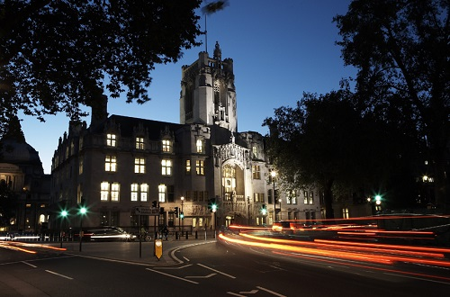 a night time photo of an impressive historic building with blurred car lights zooming past