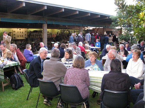 a group of people around tables at an outdoor museum