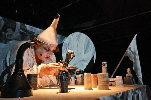 A character with a funnel on his head performing with small objects